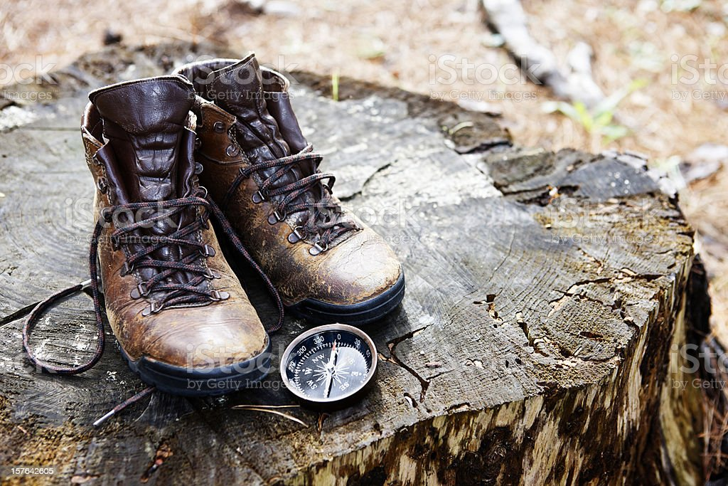Well worn hiking boots on tree stump with compass stock photo