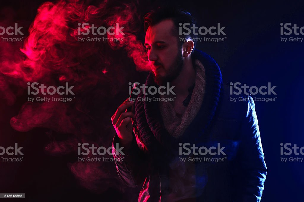 well-dressed bearded man smoking electronic cigarette in studio stock photo