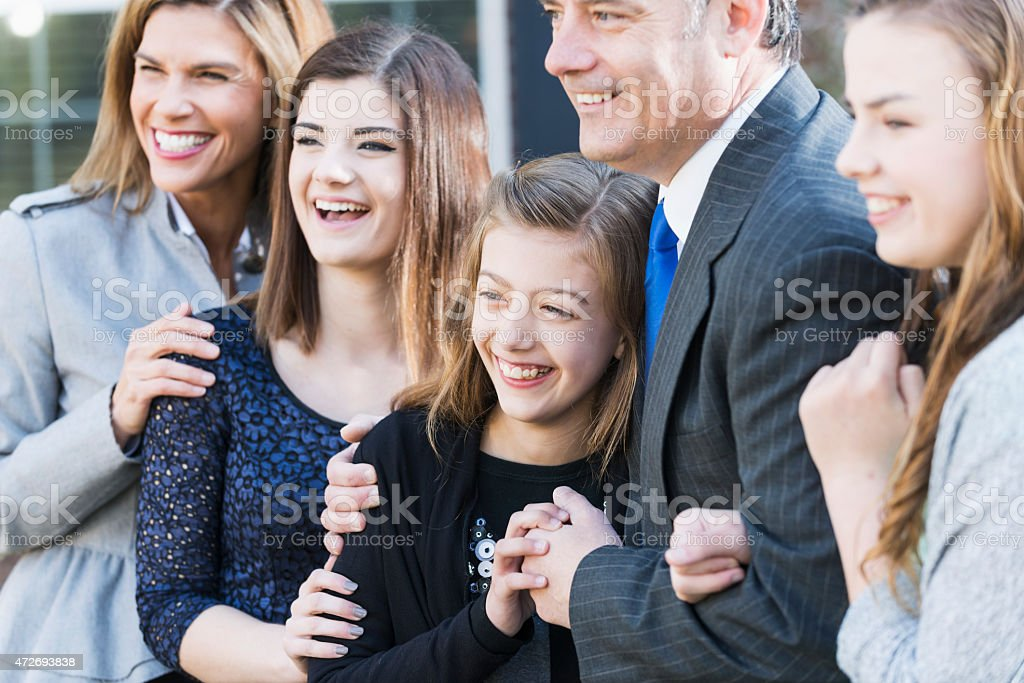 Well-dressed family, three children standing together stock photo