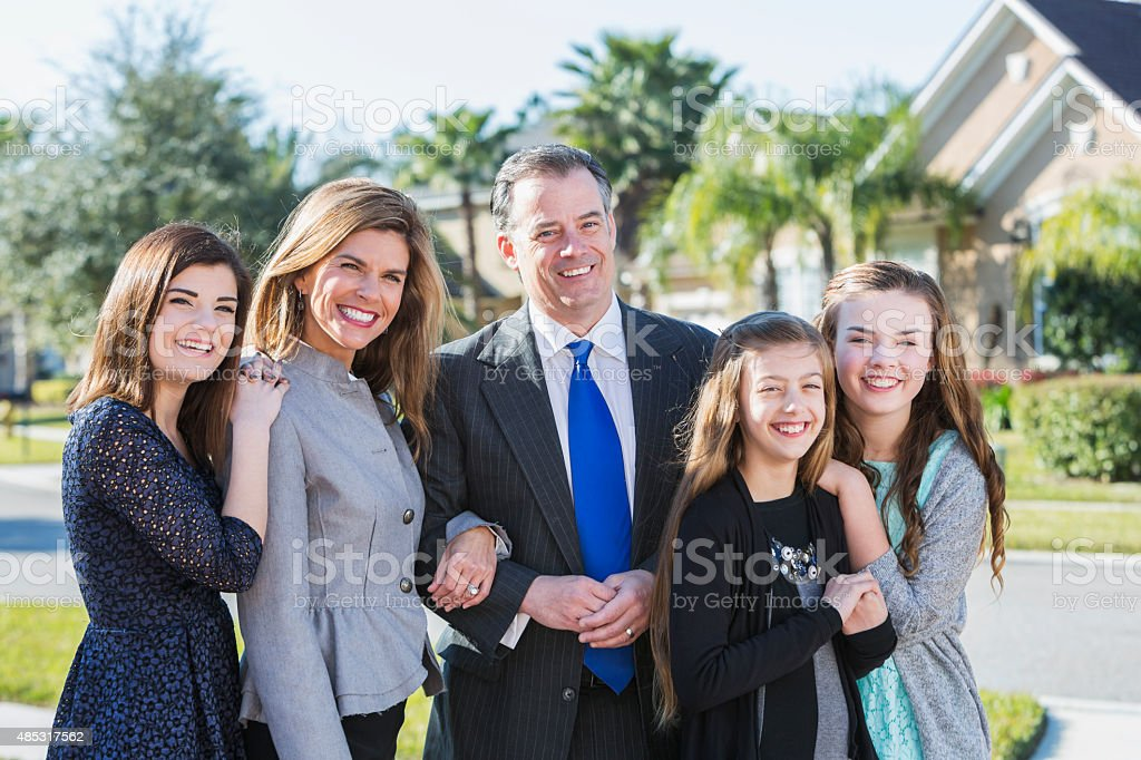 Well-dressed family with three children in front yard stock photo