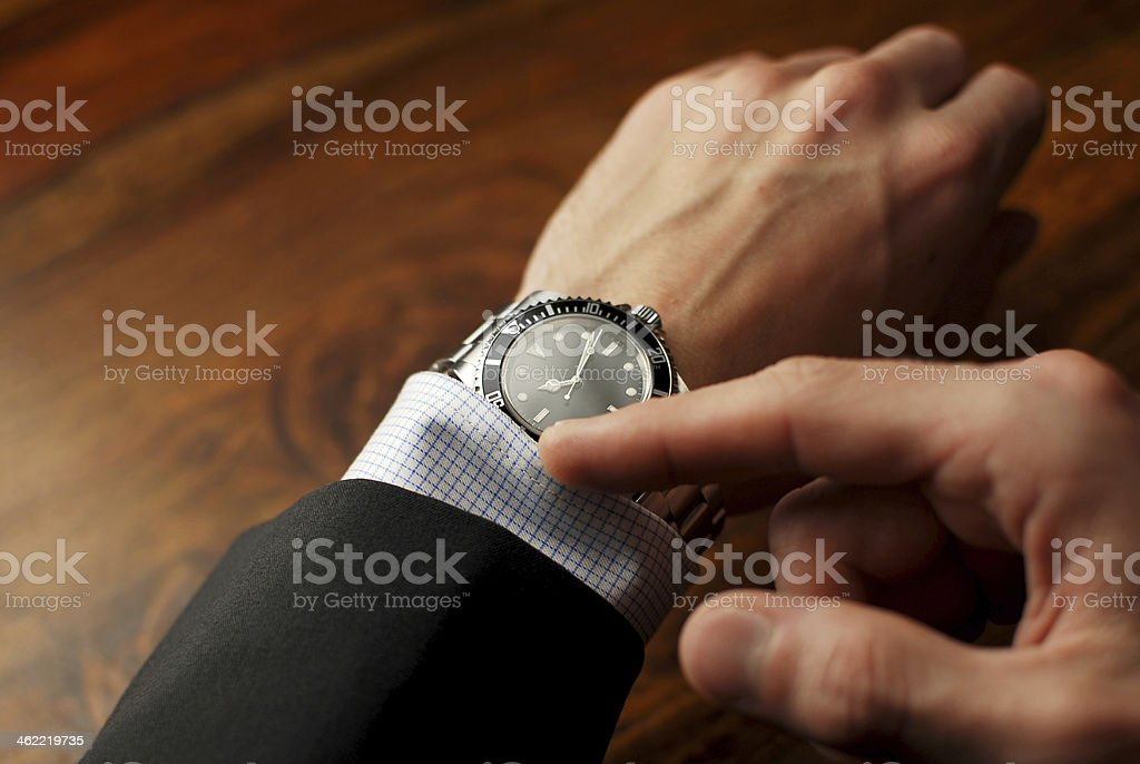 Well-dressed man checking the time on his wristwatch stock photo