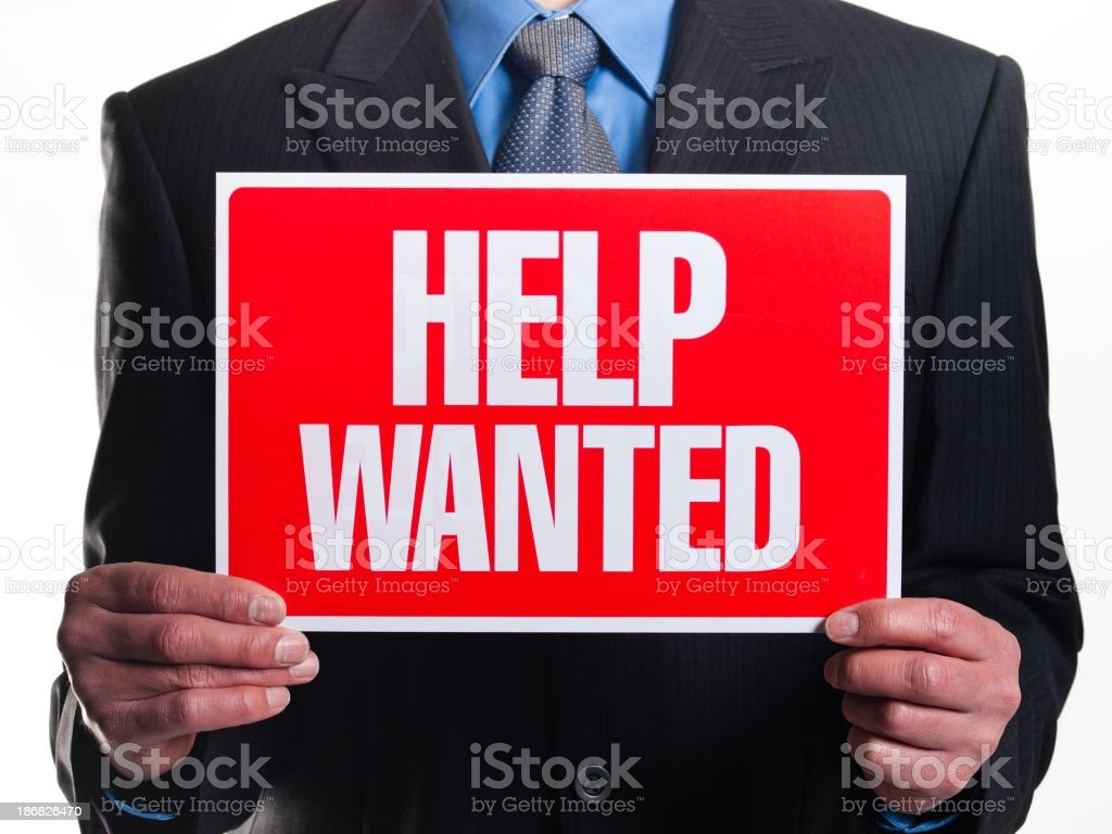 Well-dressed man holding red help wanted sign stock photo