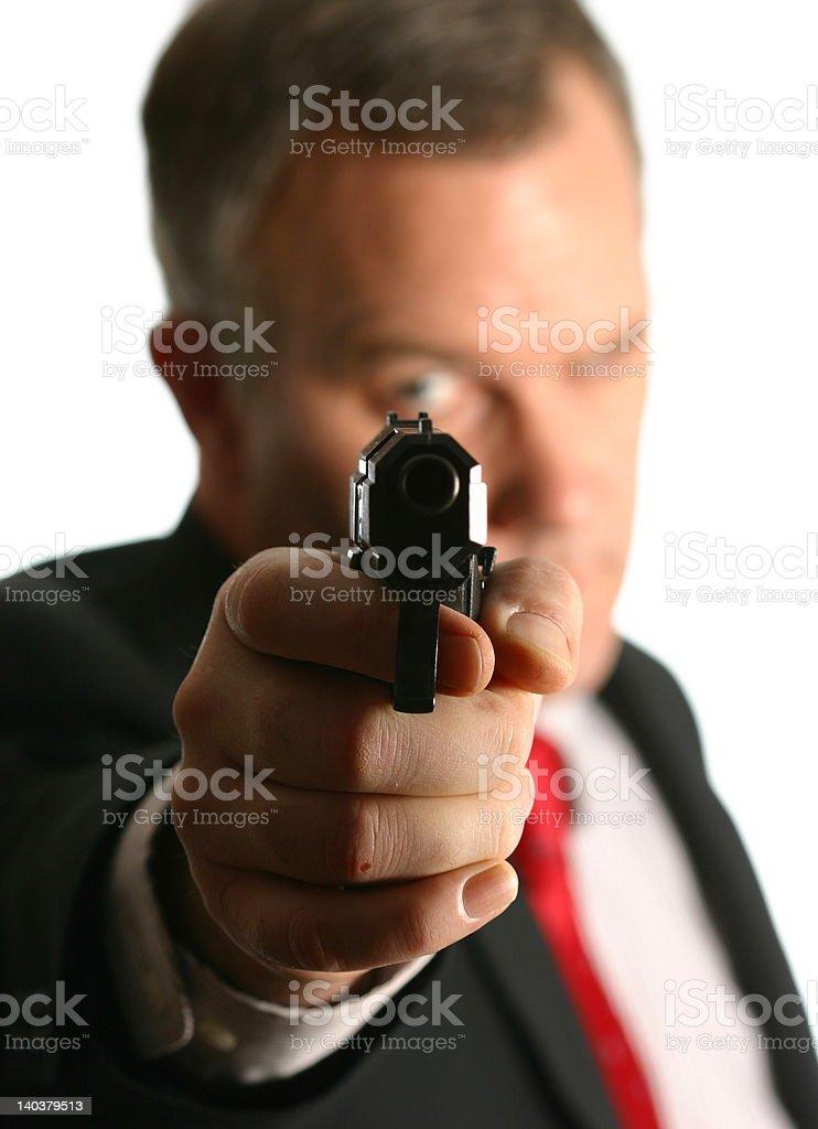 Well-dressed man pointing handgun straight at camera stock photo