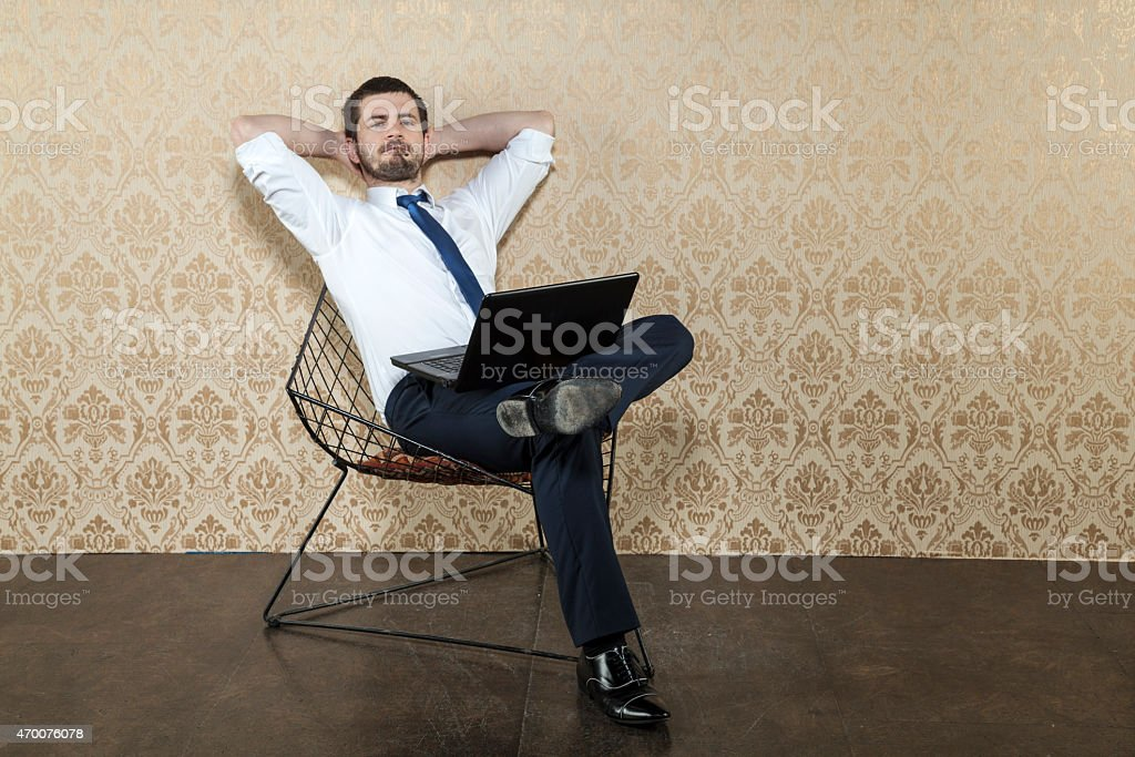Well-dressed man reclining on a chair with a laptop stock photo