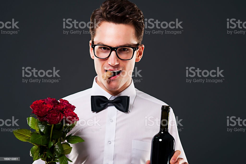 Well-dressed man with roses and wine stock photo
