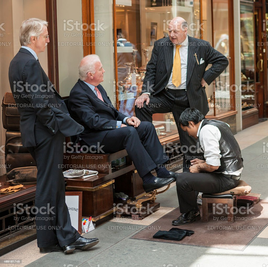 Well-dressed men at shoeshine stand off Piccadilly, London, England, UK stock photo