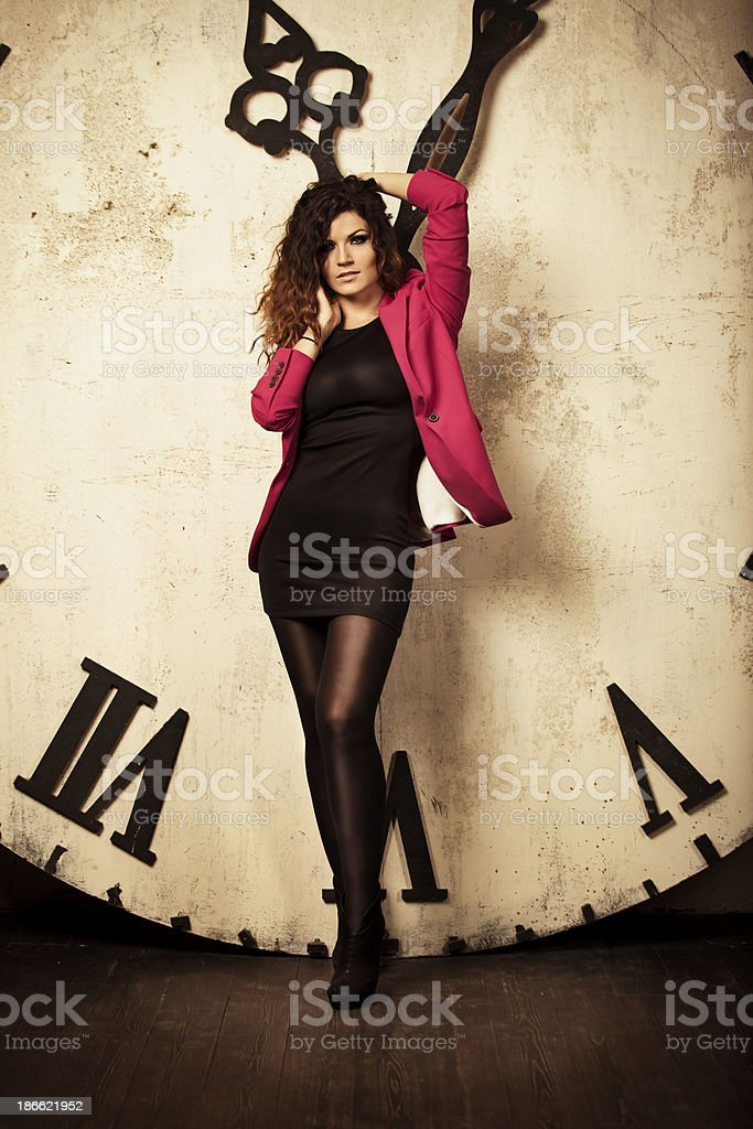 Welldressed woman standing front of large clock royalty-free stock photo
