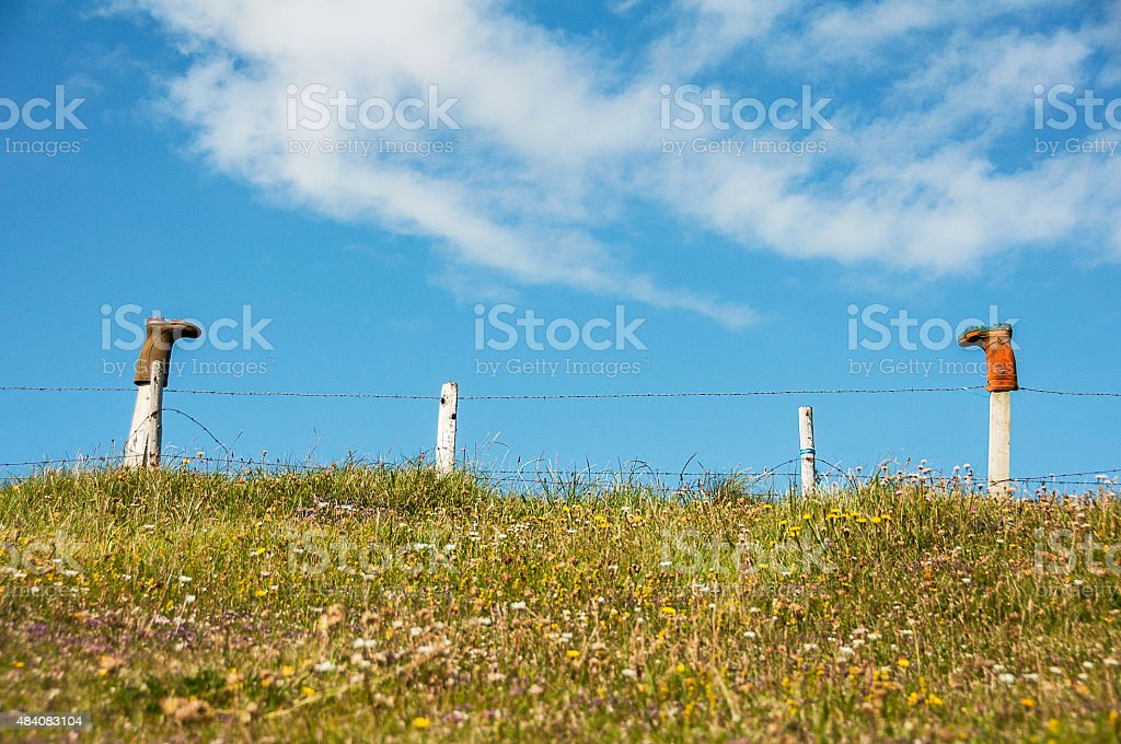 Wellington boots over a fence stock photo