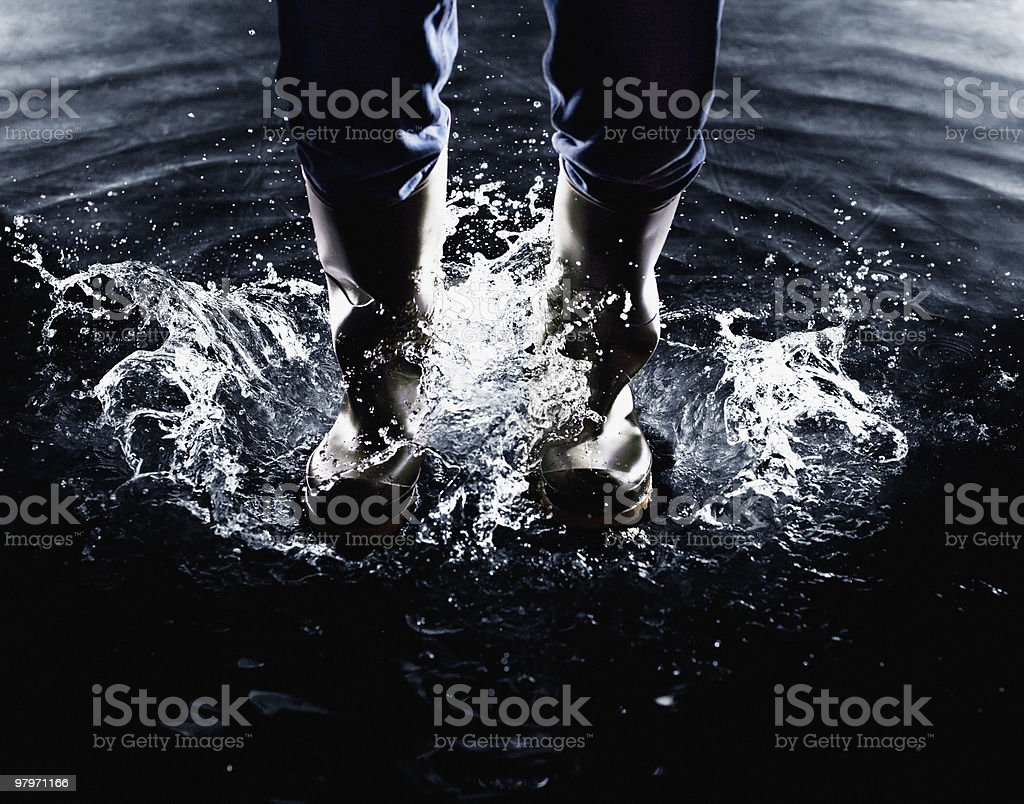 Wellingtons splashing in water stock photo