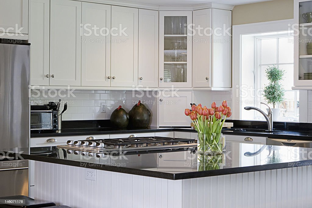 Well-lit kitchen with black granite countertop stock photo