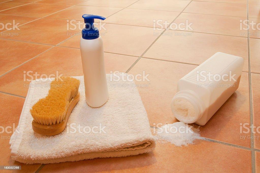 Wellness items and spilled bath-salt on brown terracotta tiled floor stock photo