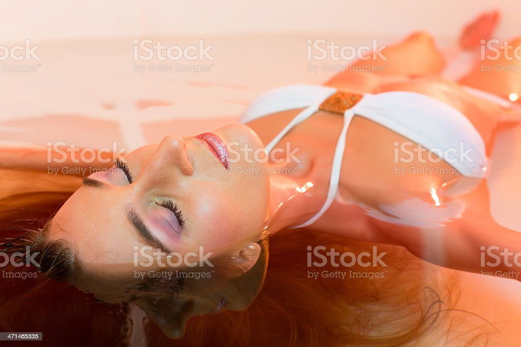 Wellness - young woman floating in Spa or swimming pool stock photo
