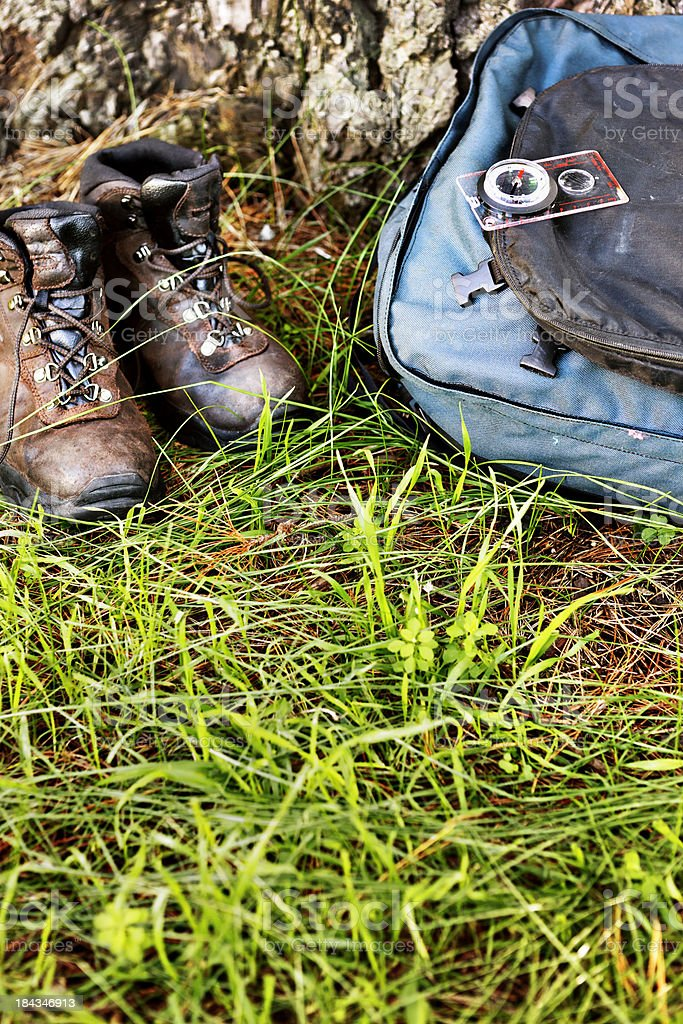 Well-worn hiking boots, backpack and compass sitting on grass royalty-free stock photo