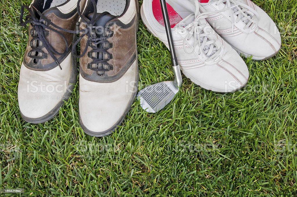 Well-worn men's and women's golf shoes stock photo