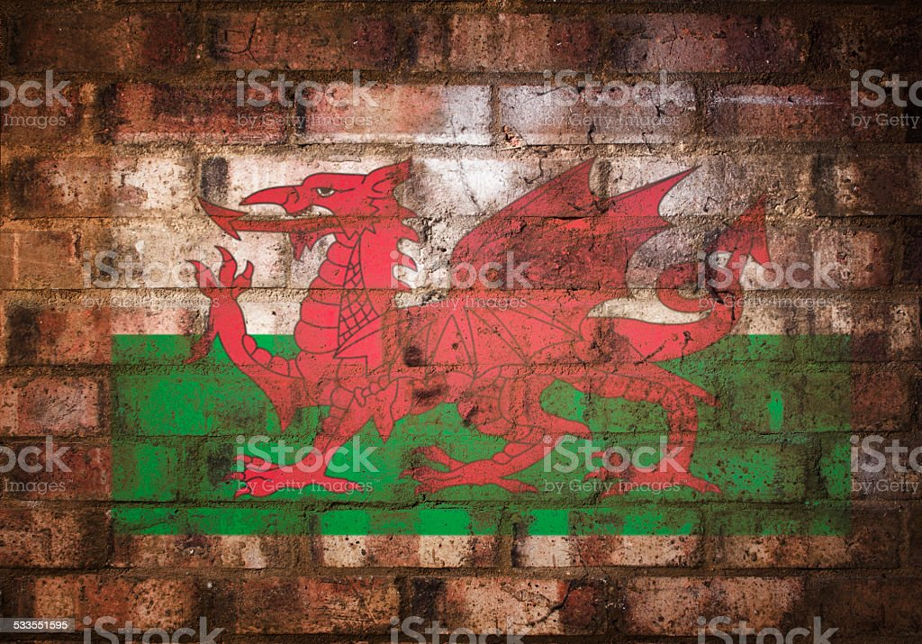 Welsh Flag Stenciled on Rustic Brick Wall stock photo