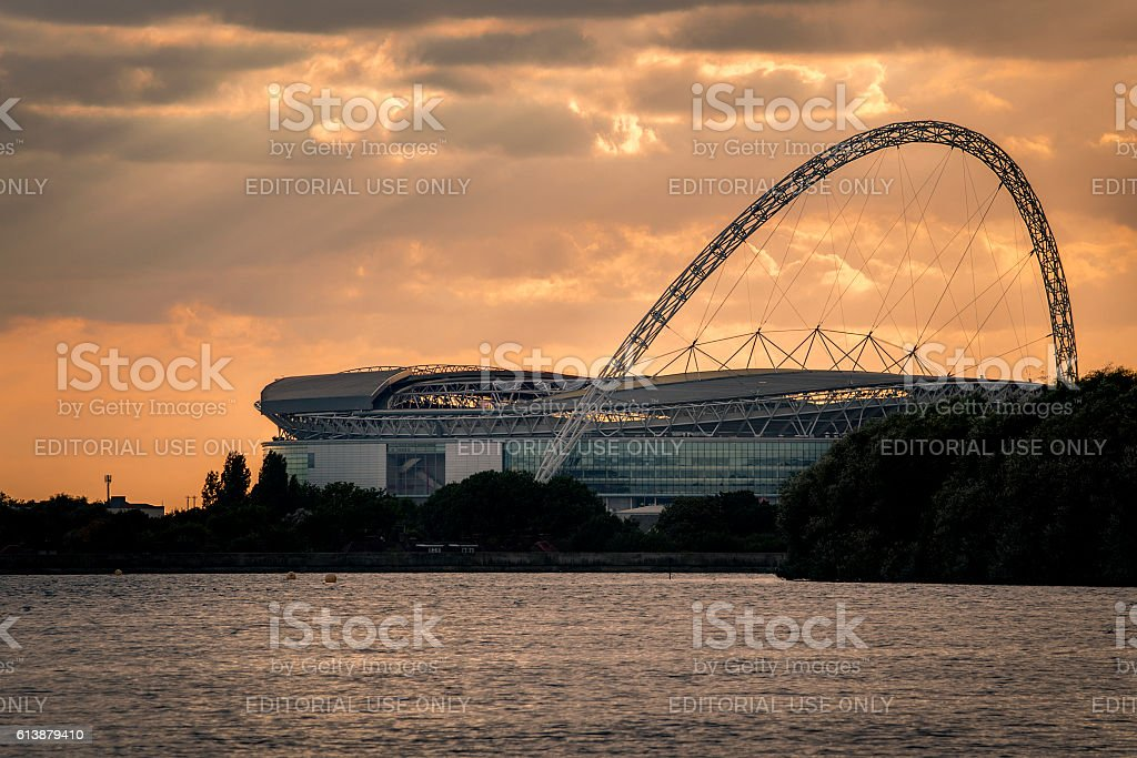 Wembley stadium at sunset from across a lake stock photo