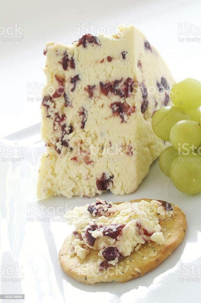 wensleydale cheesewith cranberry cheese on white platter with grapes stock photo