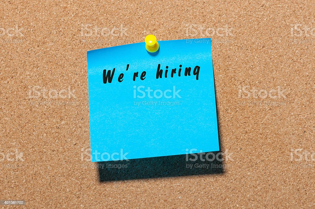 We're Hiring inscription on peace of paper pinned to stock photo