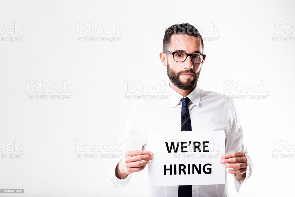 we're hiring sign shown by a businessman stock photo
