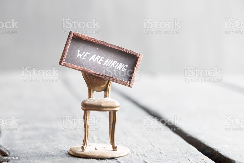 We're hiring written on chalkboard and chair stock photo