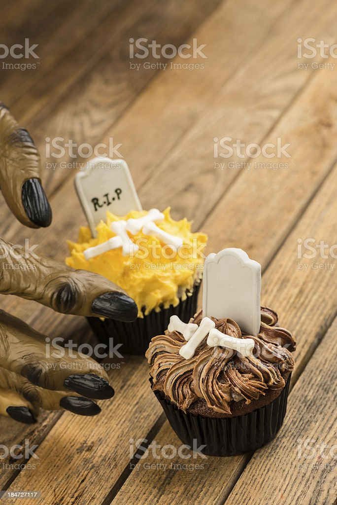 Werewolf hand reaching for a Halloween cupcake royalty-free stock photo