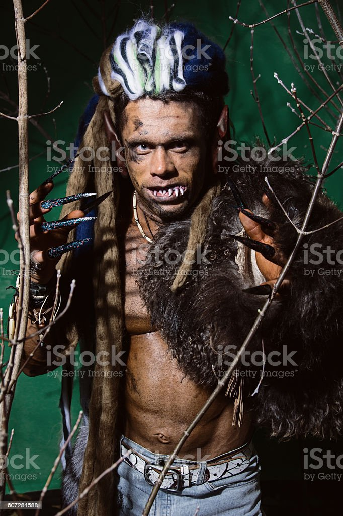 Werewolf with long nails and crooked teeth among the branches stock photo