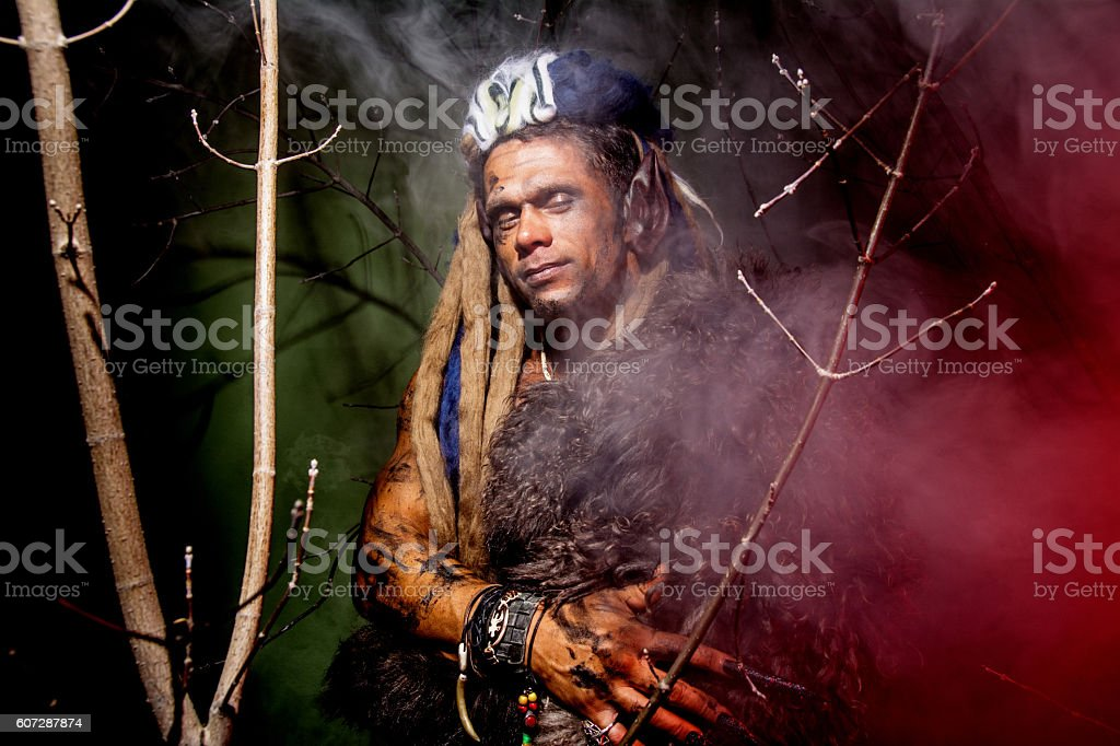 Werewolf with long nails and hair dreadlocks among the branches stock photo