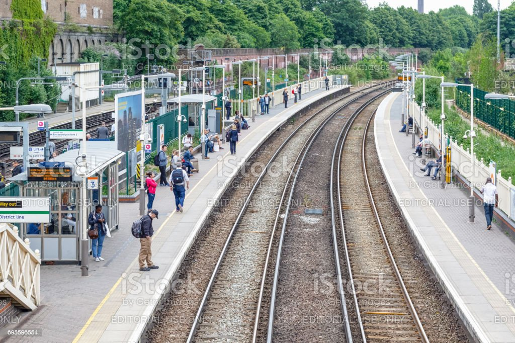 West Brompton overground station platforms, with commuters waiting on platforms stock photo