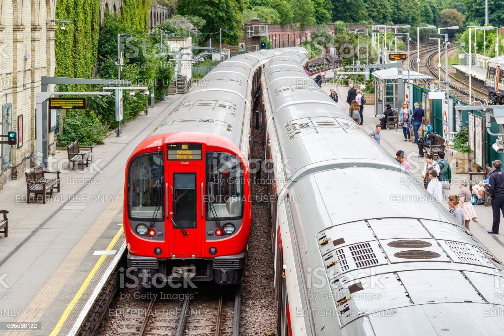 West Brompton underground station platforms, with commuters boarding the train stock photo