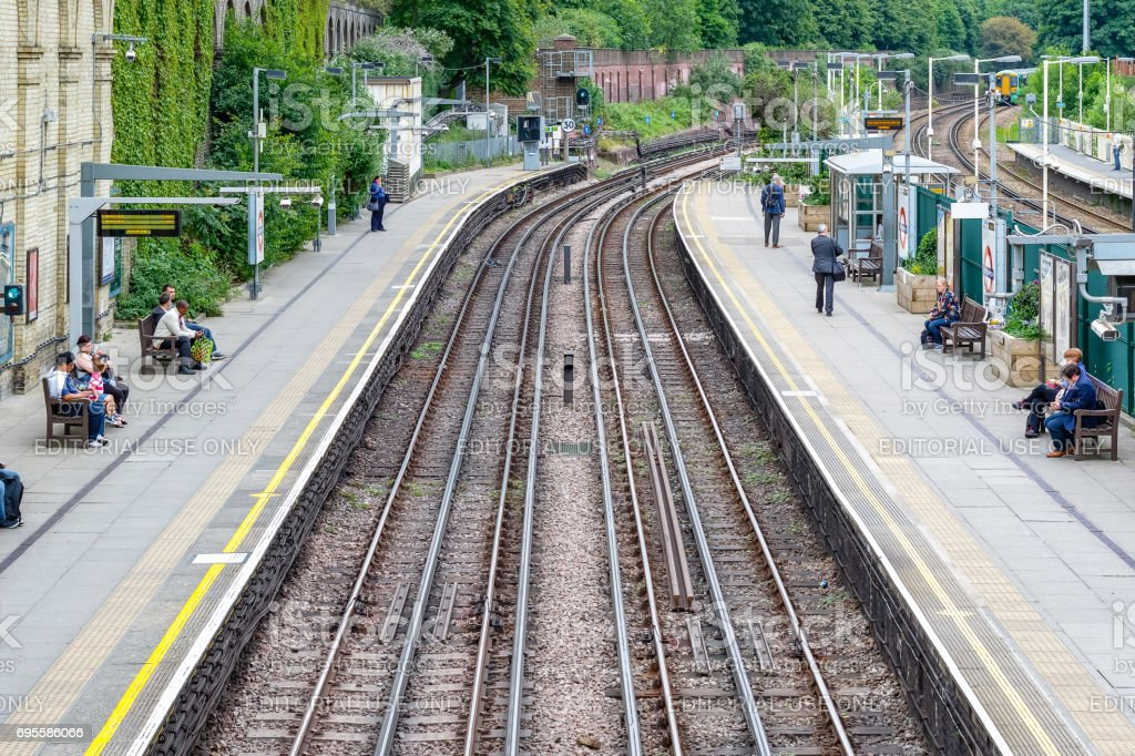 West Brompton underground station platforms, with commuters waiting on platforms stock photo
