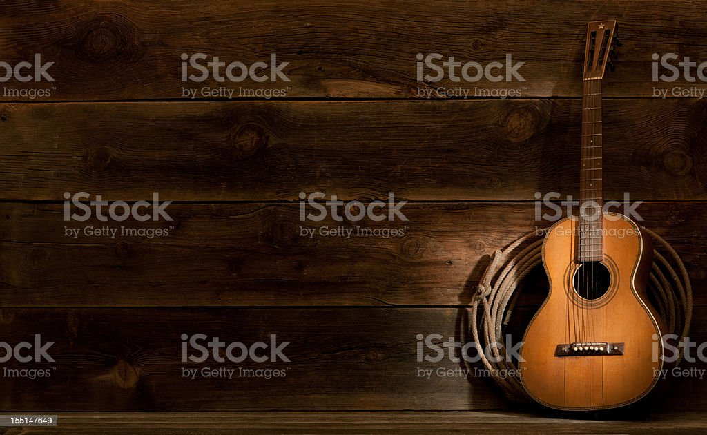 Western barnwood background w/parlor guitar & lasso stock photo