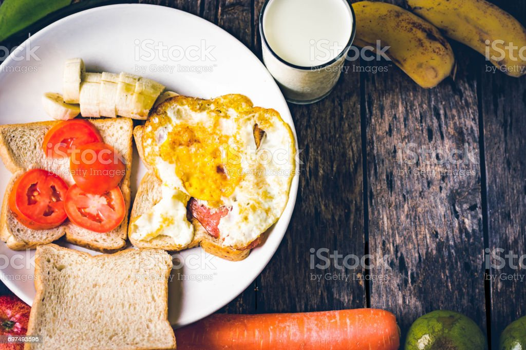Western breakfast : toast egg and fruit on wooden table stock photo