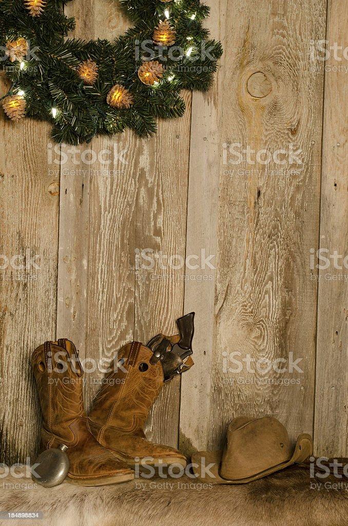 Western Christmas Scene w/boots,hat,gun and wreath-barnwood background stock photo