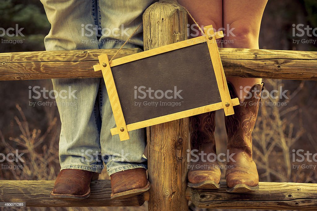 Western Couple Standing on a Fence with Chalkboard stock photo