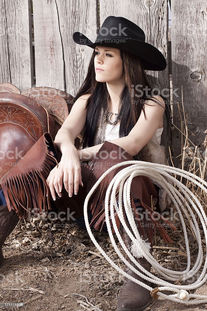 Western Cowgirl and Saddle Against Rustic Wood Fence royalty-free stock photo