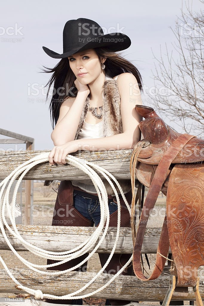Western Cowgirl and Saddle on a Rustic Wood Fence royalty-free stock photo
