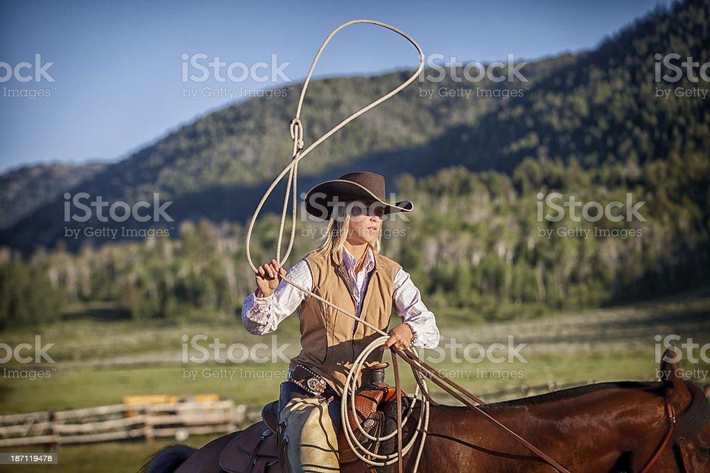 Western Cowgirl Lassoing on Horseback royalty-free stock photo