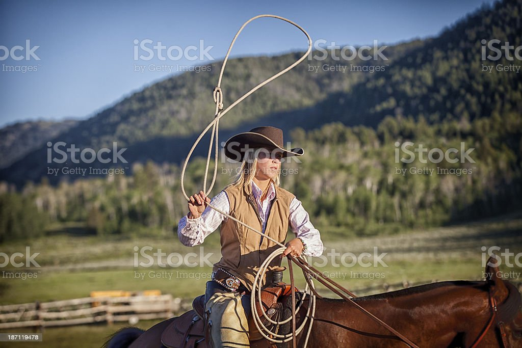 Western Cowgirl Lassoing on Horseback stock photo