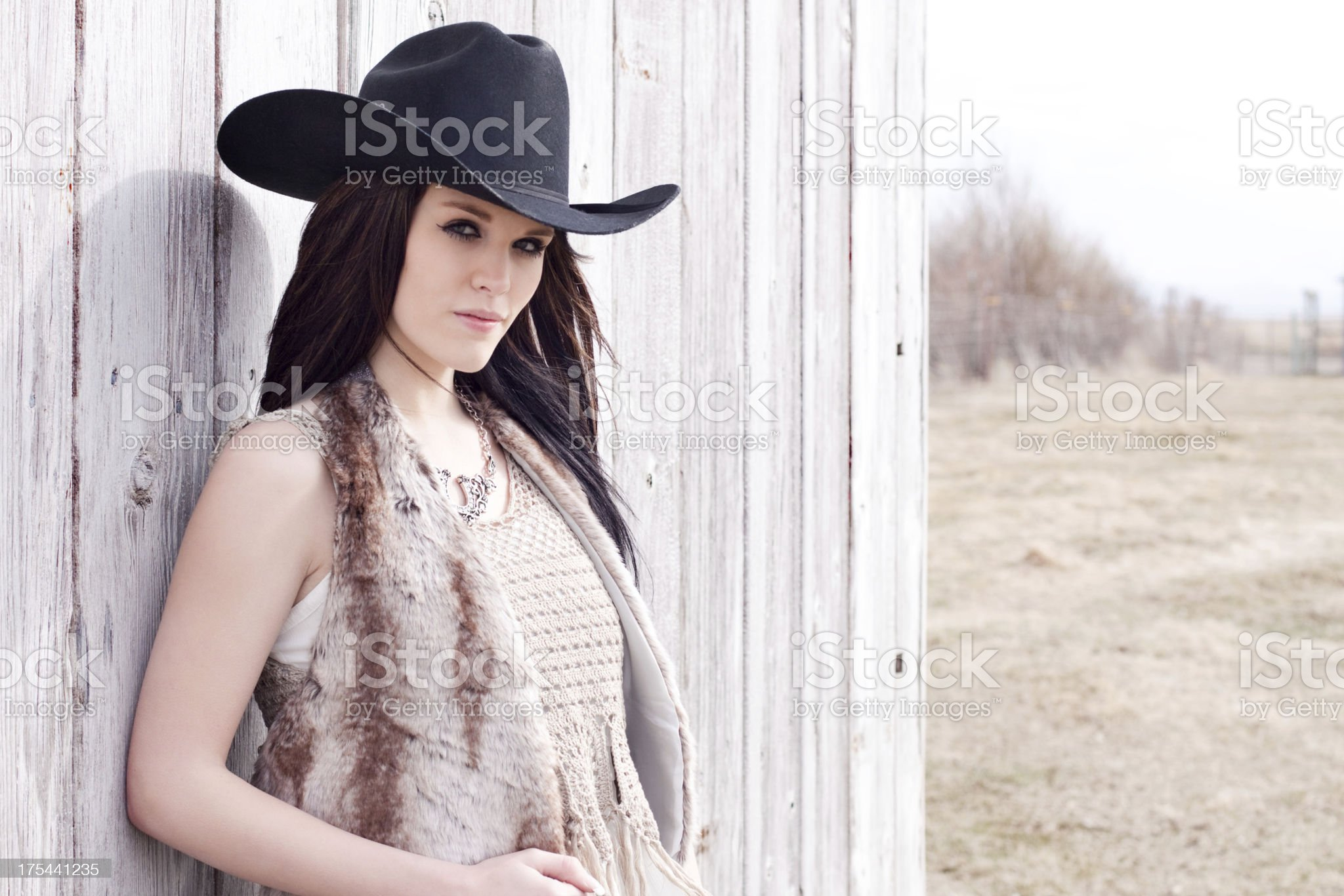 Western Cowgirl Leaning Against Rustic Wood Fence royalty-free stock photo