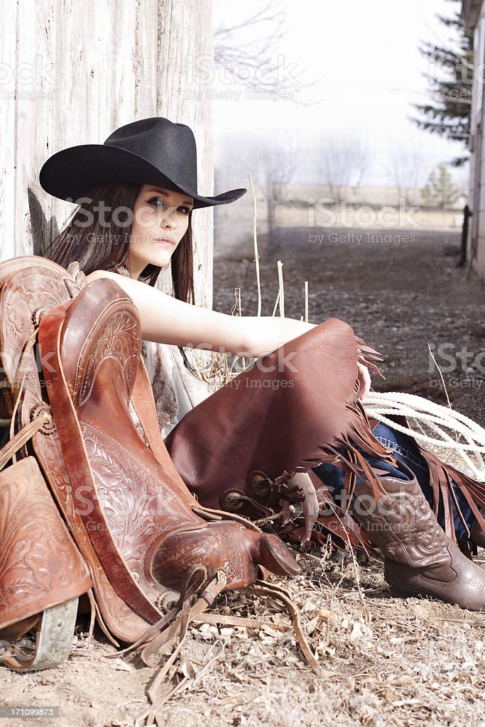 Western Cowgirl Sitting Against Rustic Wood Fence royalty-free stock photo