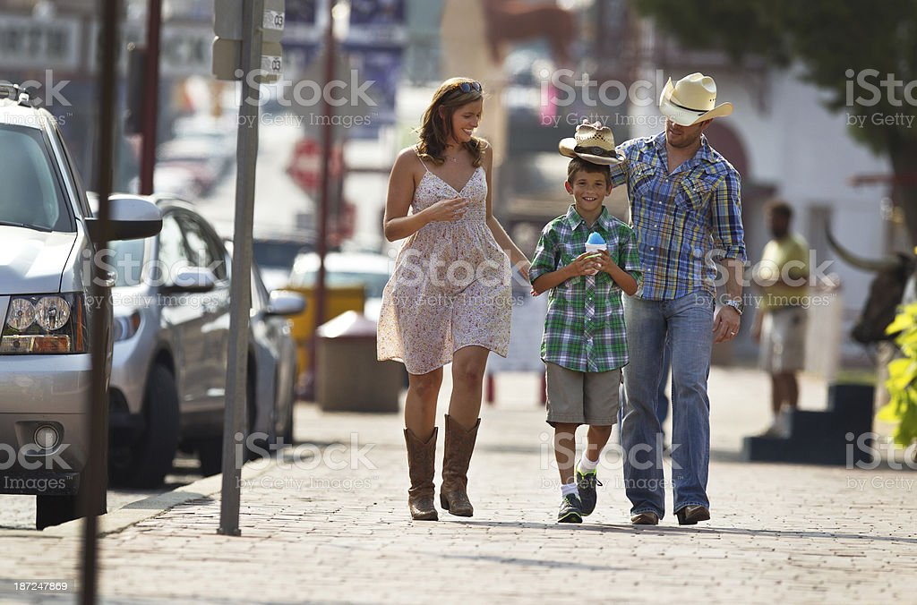 Western Family Strolling Down a Small Town U.S. Street. stock photo