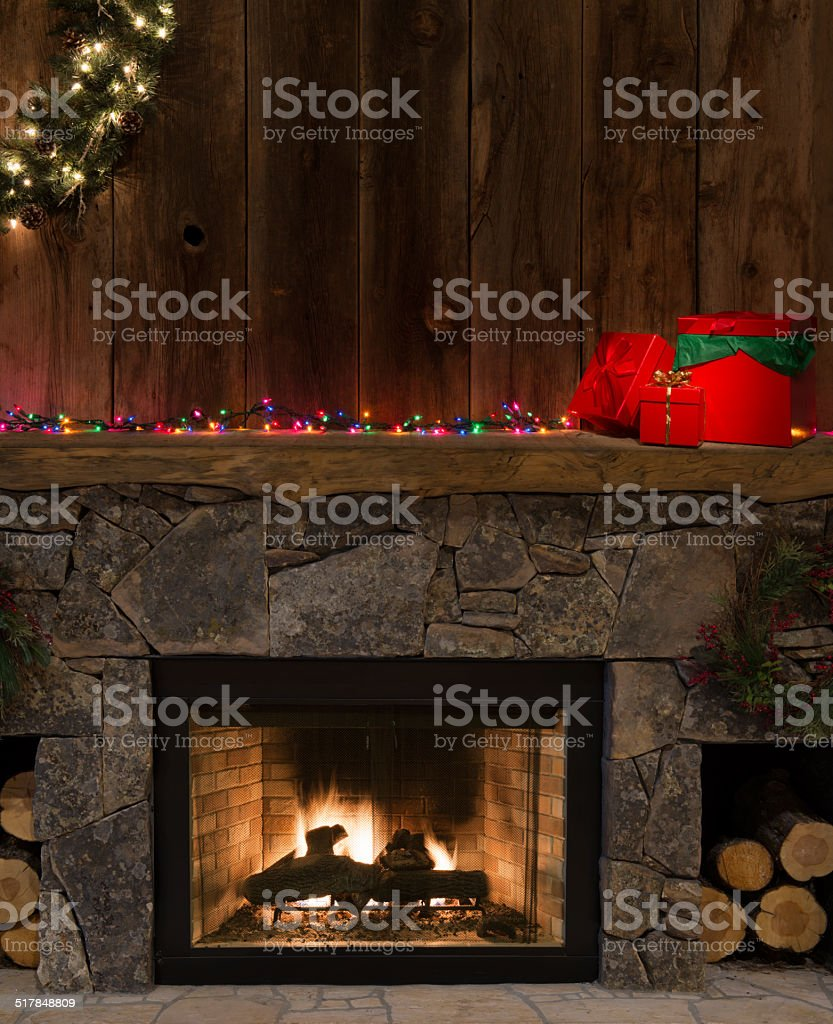 Western fireplace hearth w/Christmas decor-fire,lights,red boxes w/bows stock photo