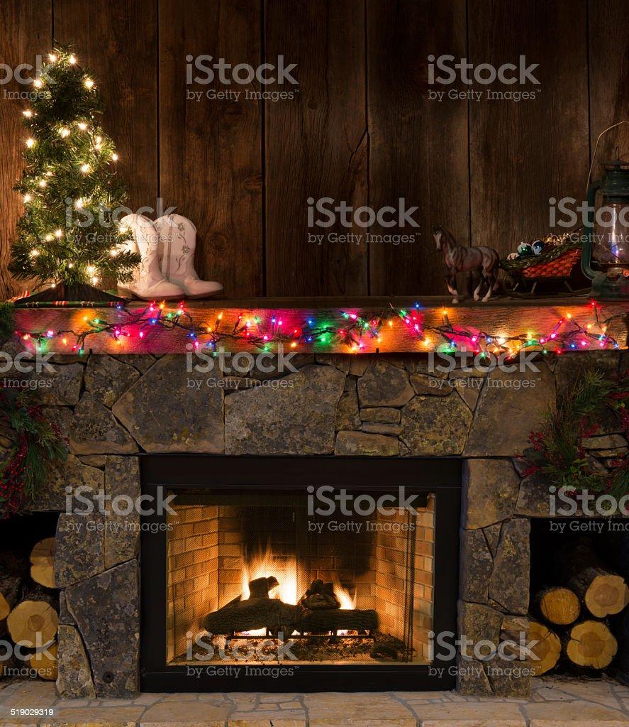 Western fireplace w/Christmas decor-fire,boots,lighted tree,sleigh,lantern stock photo