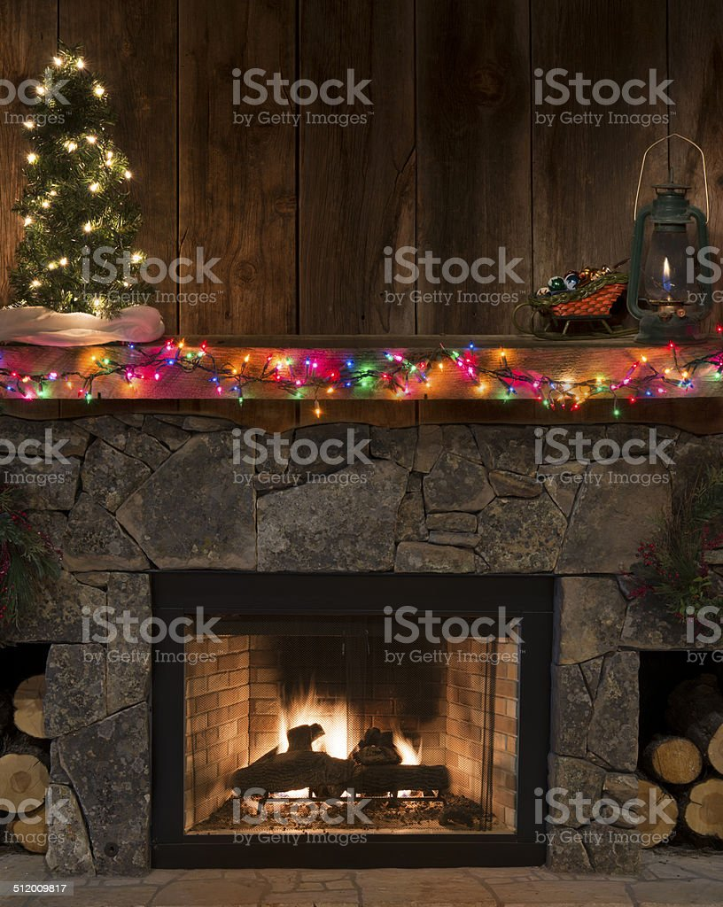 Western fireplace w/Christmas decor-lighted tree,fire,sleigh,lantern,on mantel stock photo