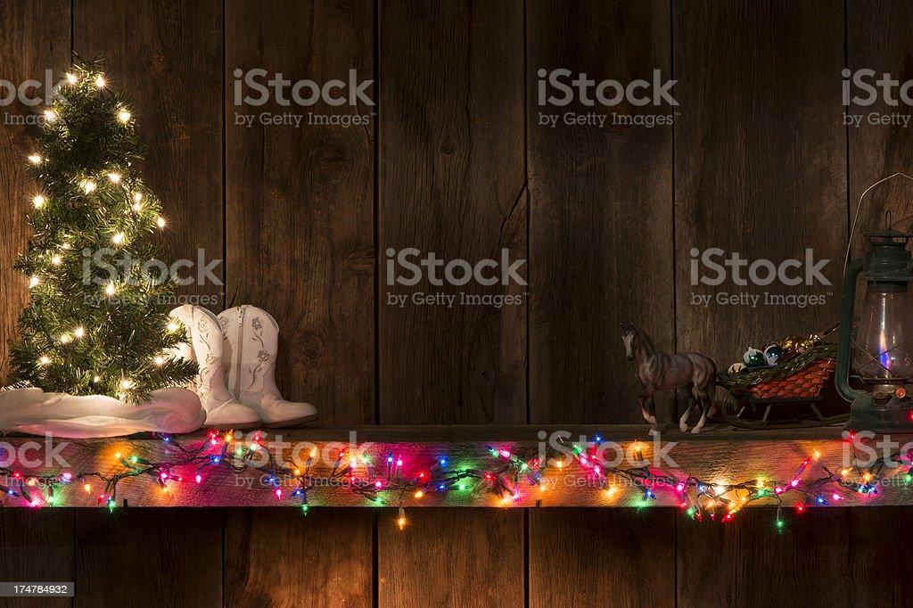 Western holiday mantel w/lights,tree,sleigh,boots-barnwood background stock photo