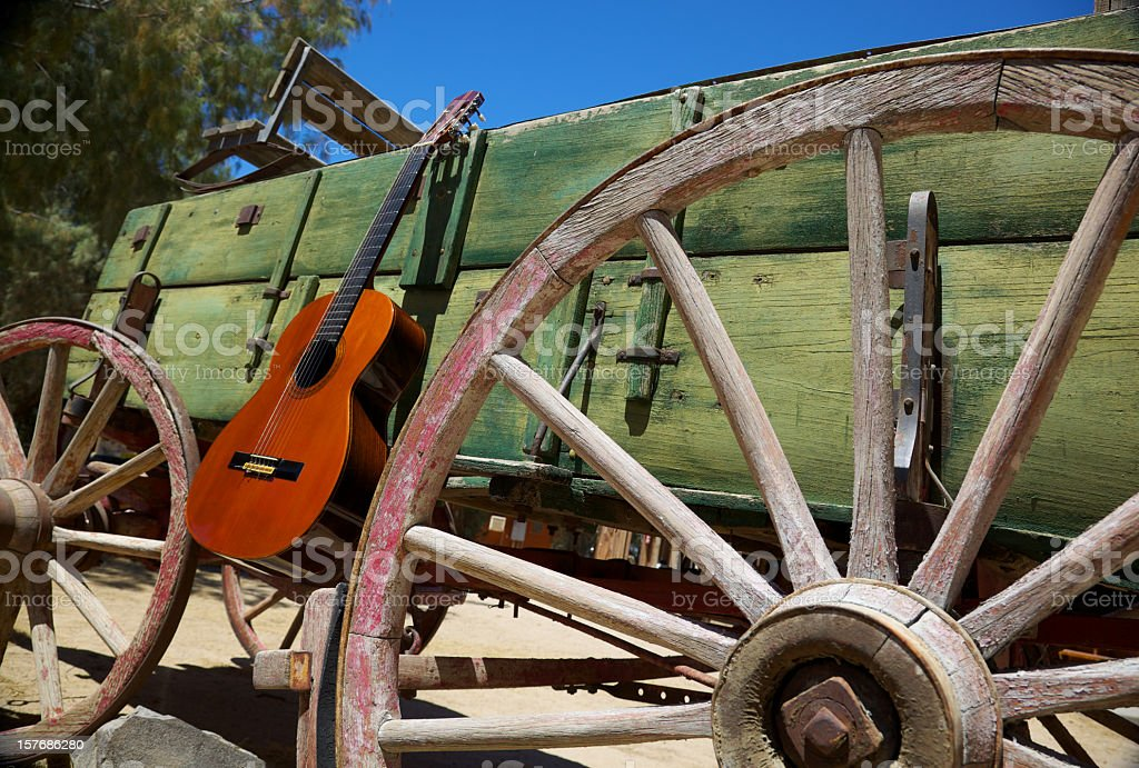Western Music Guitar and Wagon Wheel in Old West stock photo
