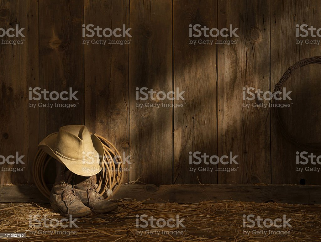 Western packer's boots,hat,lasso on barn floor-sunbeam on barnwood wall stock photo