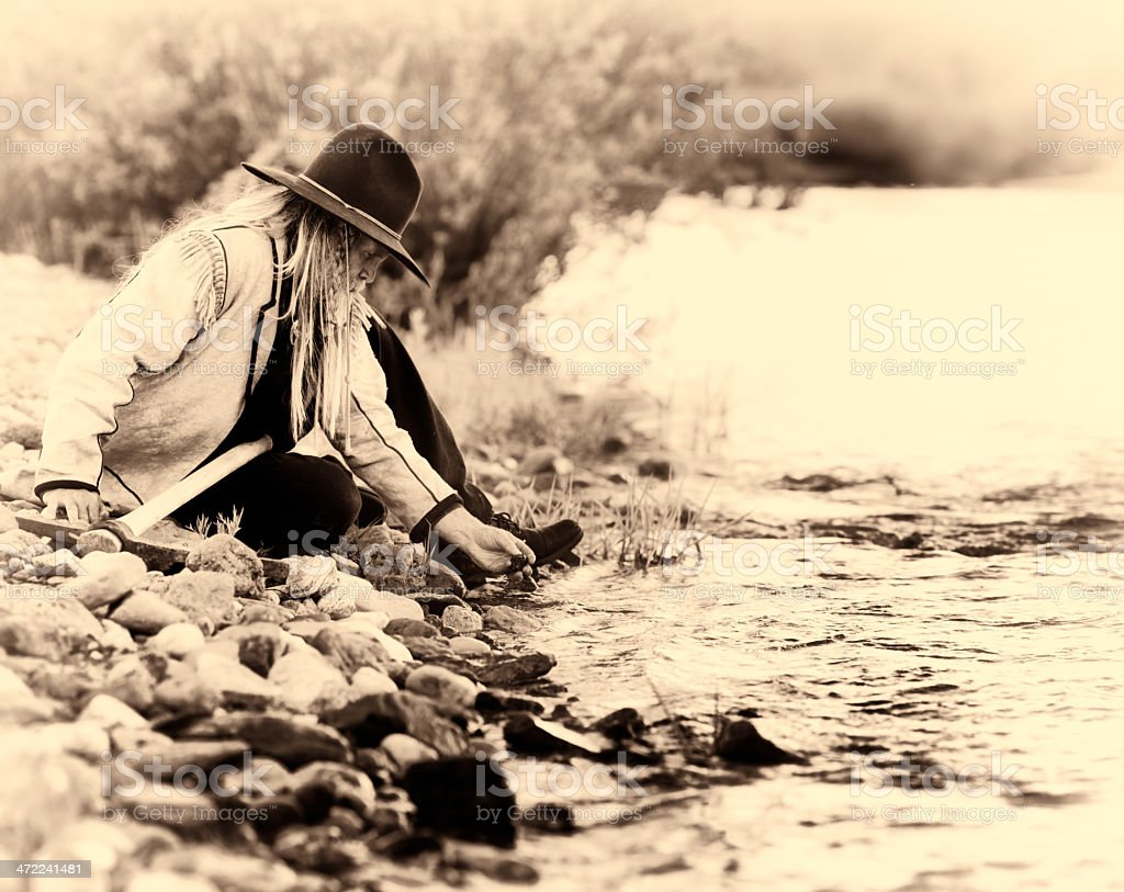 Western prospector picks up pebbles from river bed stock photo