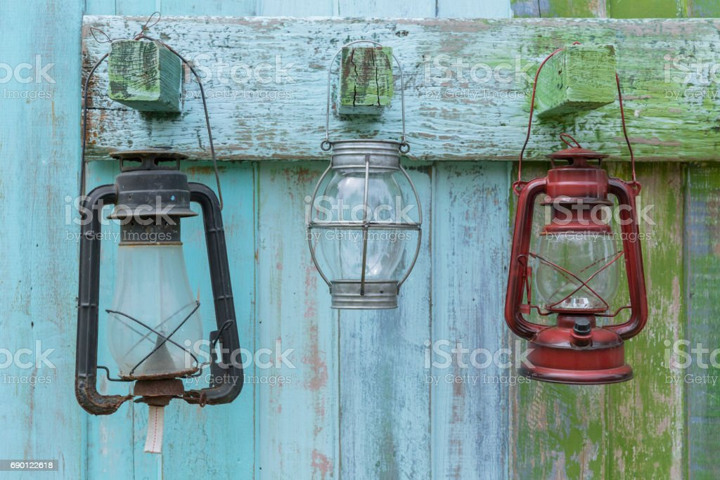 Western style oil lantern hanging at farm countryside, old lamp vintage style hang on wood background. stock photo