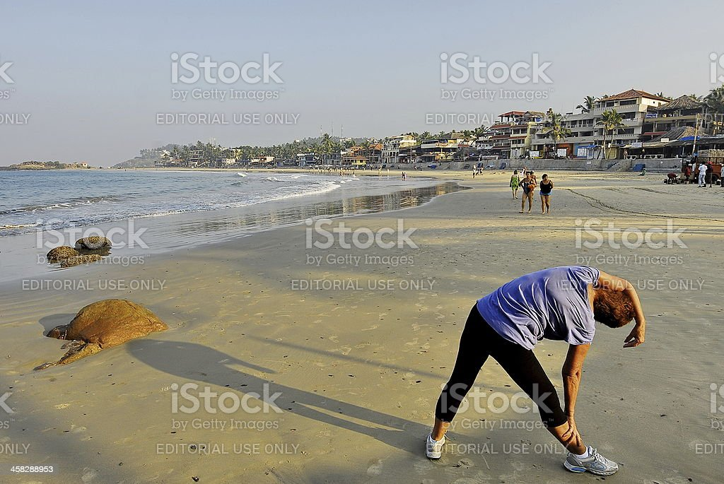 Western tourist does exercises on a beach in Kerala, India. stock photo